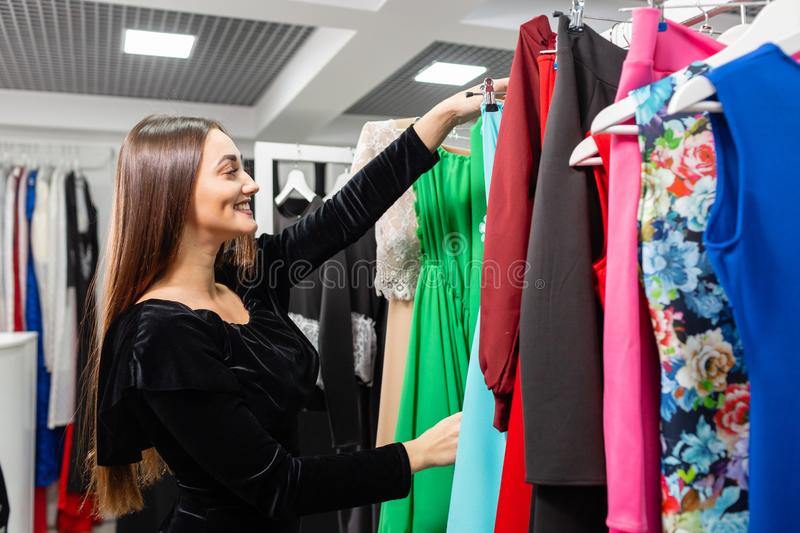 Happy young woman choosing clothes in mall or clothing store. royalty free stock photo