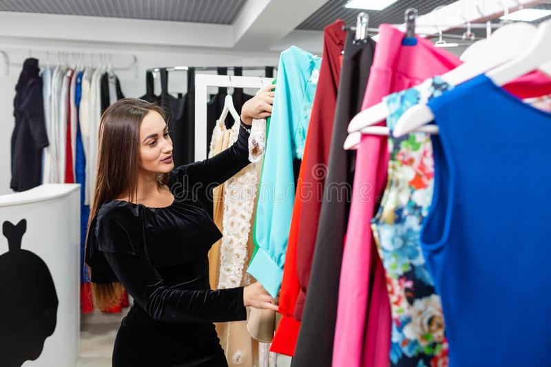Happy young woman choosing clothes in mall or clothing store. royalty free stock image