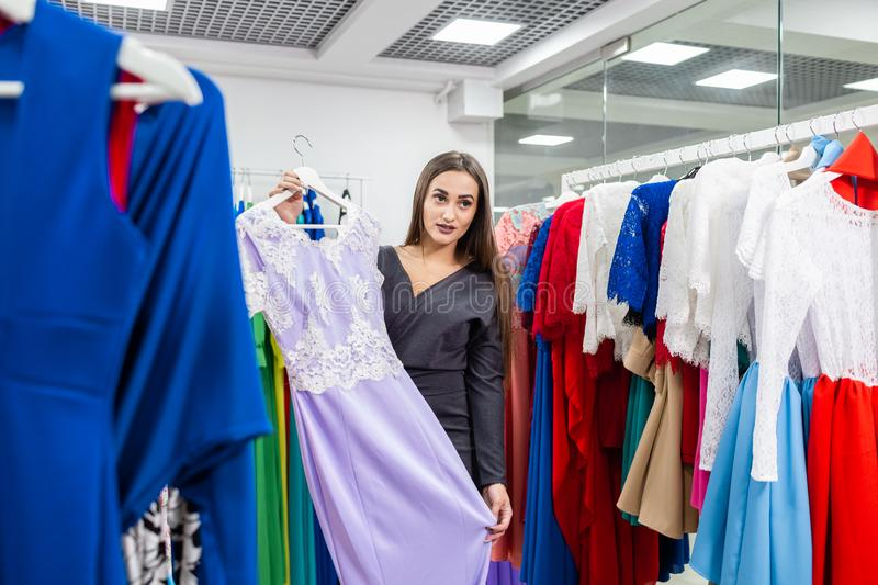 Beautiful girl with lilac dress near mirror on room background. Happy young woman choosing clothes in mall or clothing royalty free stock photos