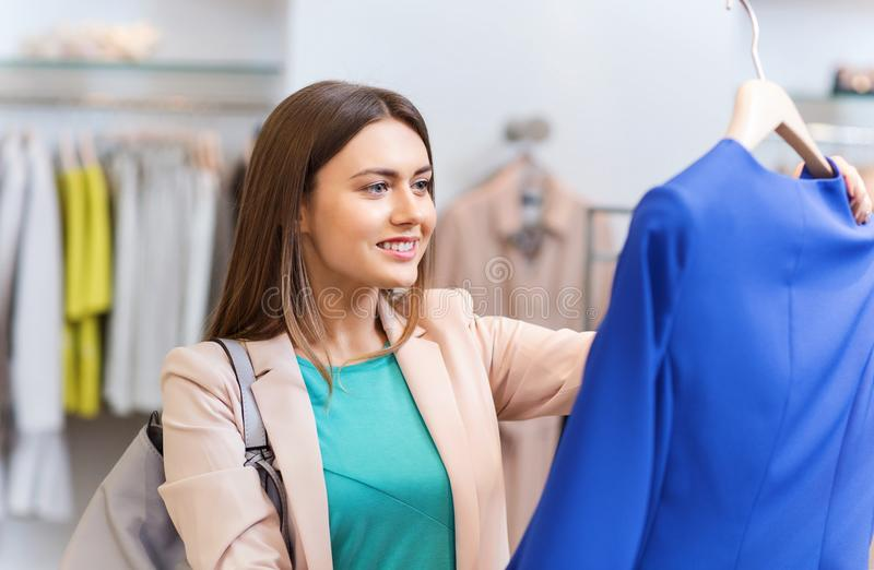 Happy young woman choosing clothes in mall. Sale, shopping, fashion, style and people concept - happy young woman choosing clothes in mall or clothing store stock photo