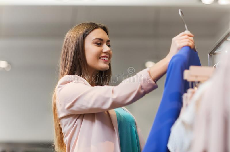 Happy young woman choosing clothes in mall. Sale, shopping, fashion, style and people concept - happy young woman choosing clothes in mall or clothing store stock photos