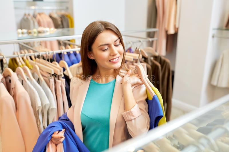 Happy young woman choosing clothes in mall. Shopping, fashion, sale and people concept - happy young woman with clothes on hangers in mall or clothing store stock image
