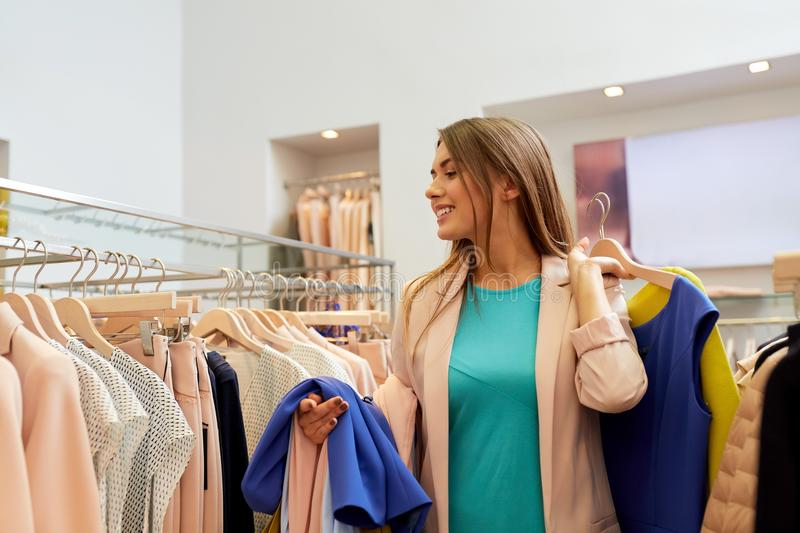 Happy young woman choosing clothes in mall. Shopping, fashion, sale and people concept - happy young woman with clothes on hangers in mall or clothing store royalty free stock image