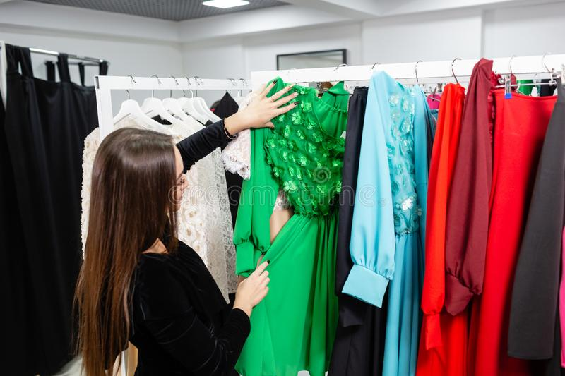 Happy young woman choosing clothes in mall or clothing store. royalty free stock photography