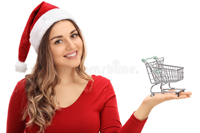 Happy young woman with Christmas hat holding small empty shopping cart royalty free stock photography
