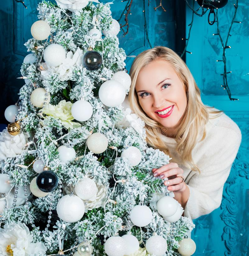 Woman with a Christmas tree. Happy young woman with a Christmas tree at home stock image