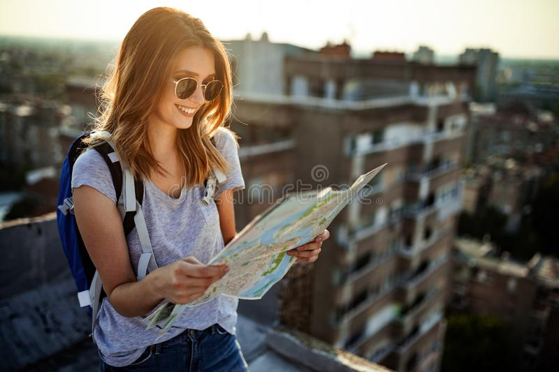 Happy young woman with a city map and a backpack travelling royalty free stock photo
