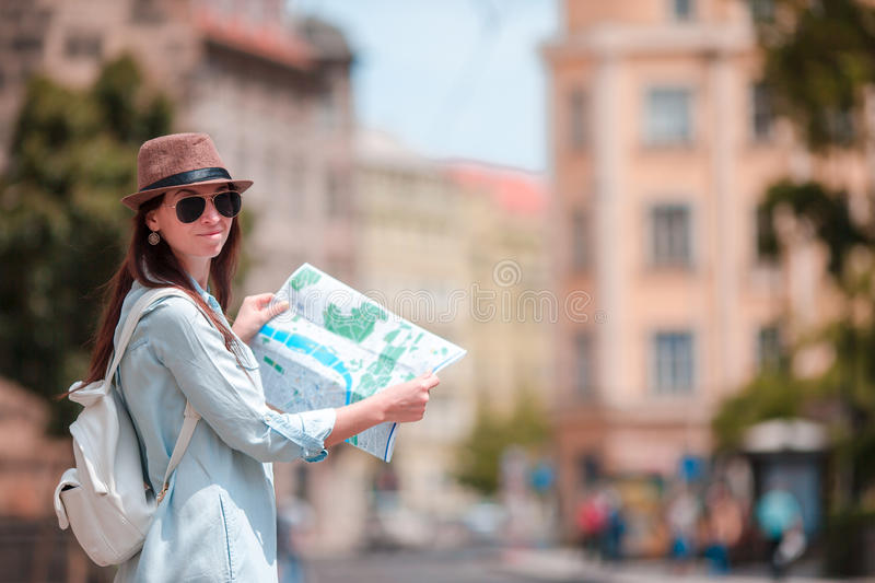 Happy young woman with a city map in city. Travel tourist woman with map in Prague outdoors during holidays in Europe. Travel tourist woman with map in Prague royalty free stock photos