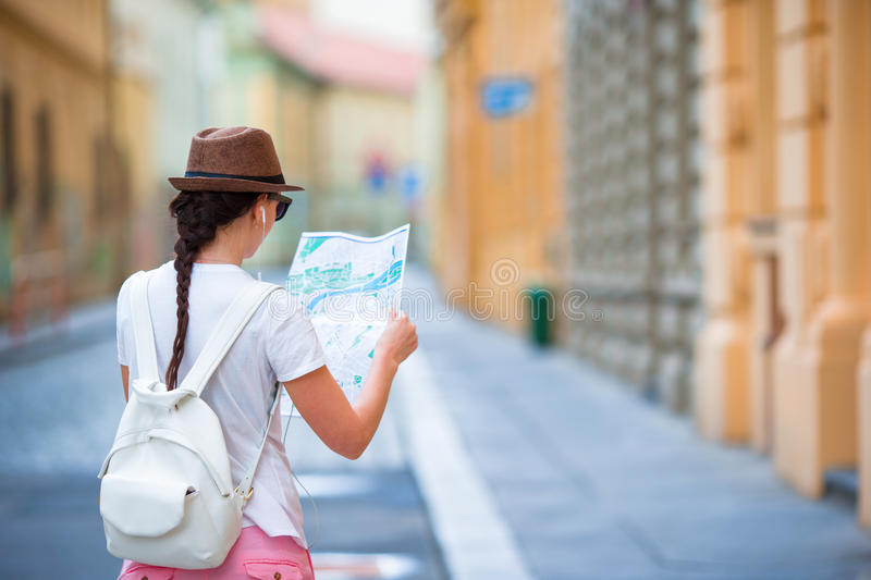 Happy young woman with a city map in city. Travel tourist woman with map in Prague outdoors during holidays in Europe. Travel tourist woman with map in Prague royalty free stock images