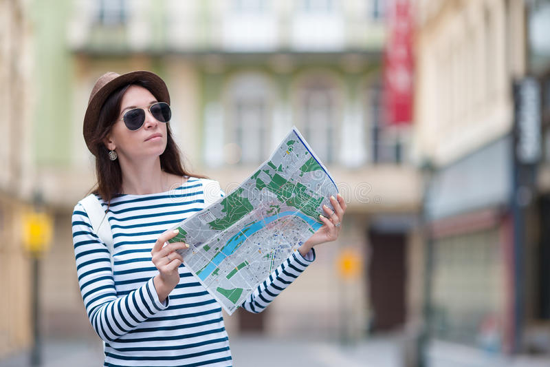 Happy young woman with a city map in Europe. Travel tourist woman with map in Prague outdoors during holidays in Europe. Travel tourist woman with map in Prague royalty free stock image