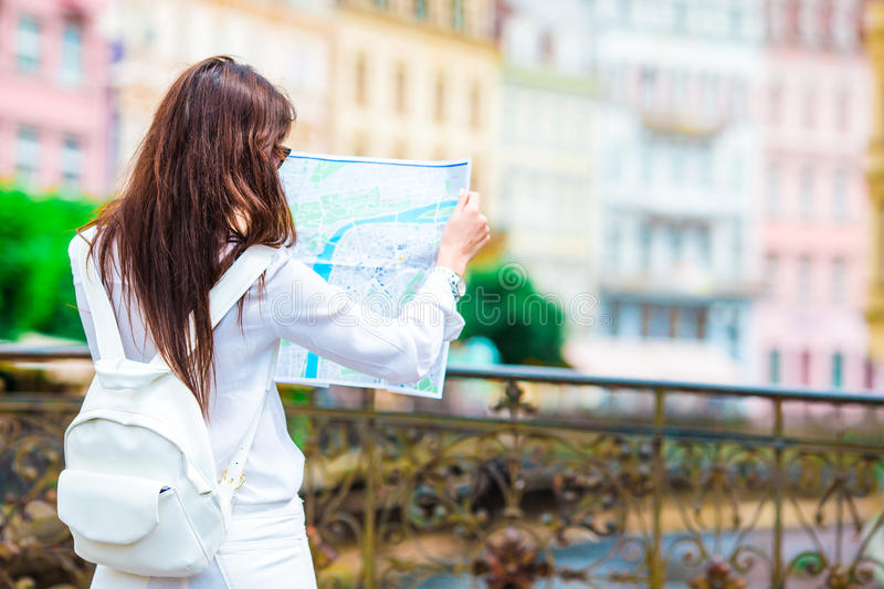 Happy young woman with a city map in Europe. Travel tourist woman with map in Prague outdoors during holidays in Europe. Travel tourist woman with map in Prague royalty free stock images