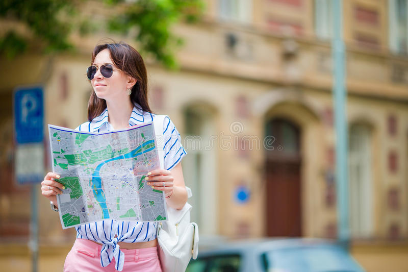 Happy young woman with a city map in Europe. Travel tourist woman with map in Prague outdoors during holidays in Europe. Travel tourist woman with map in Prague royalty free stock photography