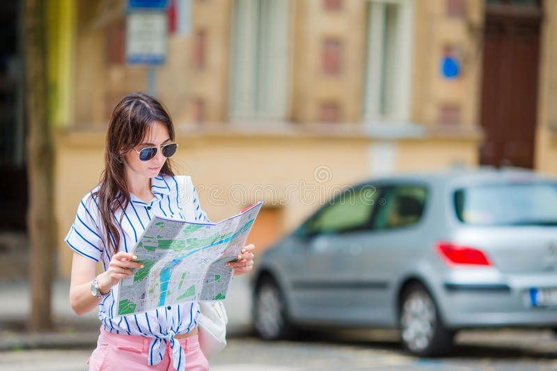Happy young woman with a city map in Europe. Travel tourist woman with map in Prague outdoors during holidays in Europe. Travel tourist woman with map in Prague stock photos