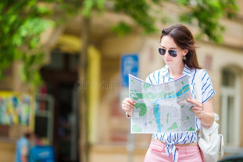 Happy young woman with a city map in Europe. Travel tourist woman with map in Prague outdoors during holidays in Europe. Travel tourist woman with map in Prague royalty free stock photos