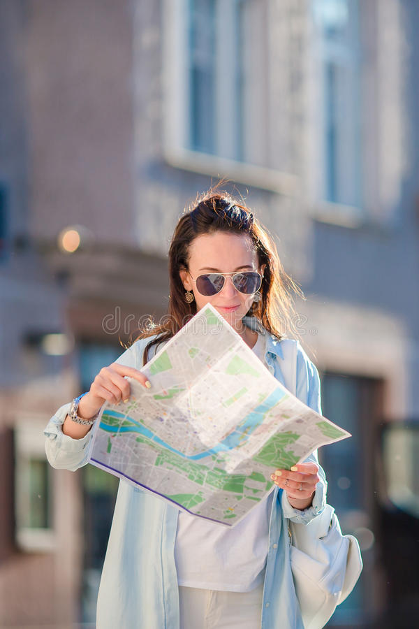 Happy young woman with a city map in Europe. Travel tourist woman with map in Prague outdoors during holidays in Europe. Travel tourist woman with map in Prague stock photography