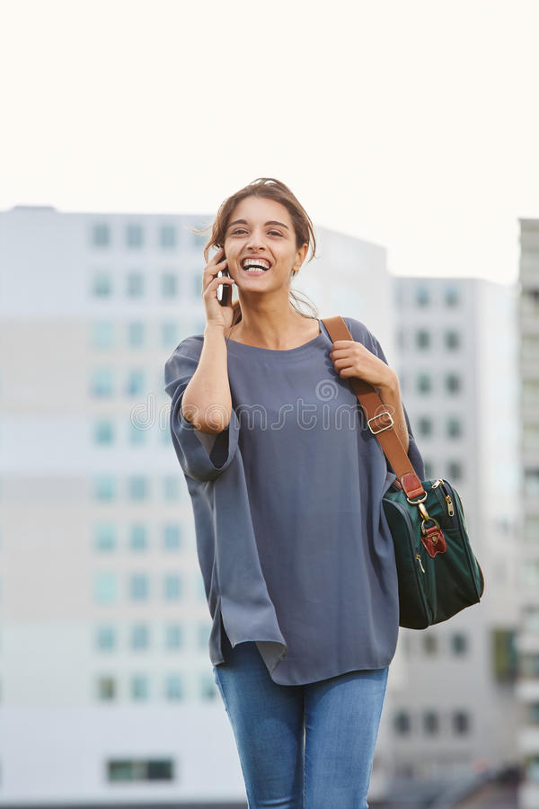 Happy young woman in city using mobile phone. Portrait of happy young woman walking in city and talking on mobile phone royalty free stock image