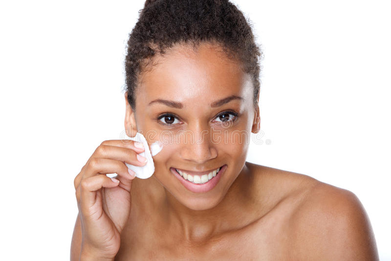 Happy young woman cleaning face with beauty sponge stock photos