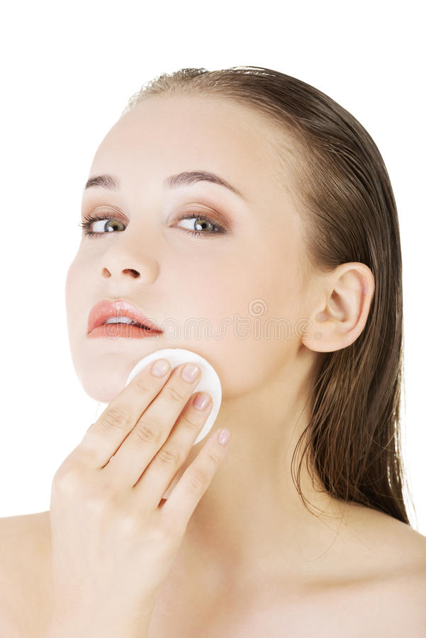 Happy young woman cleaning skin by cotton pad stock photo