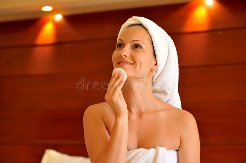 Happy young woman cleansing her face royalty free stock photography