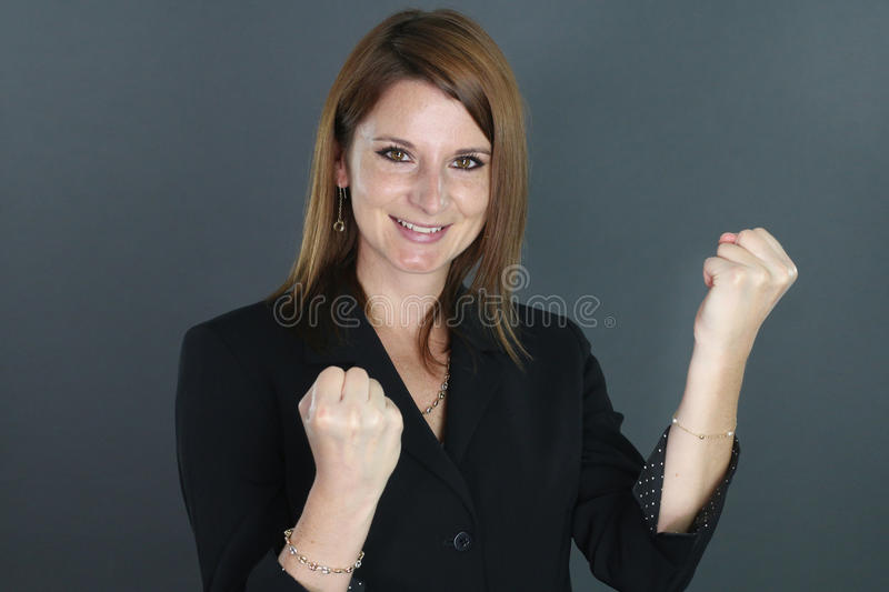 Happy young woman clenching his fists. Over a gray background royalty free stock photo