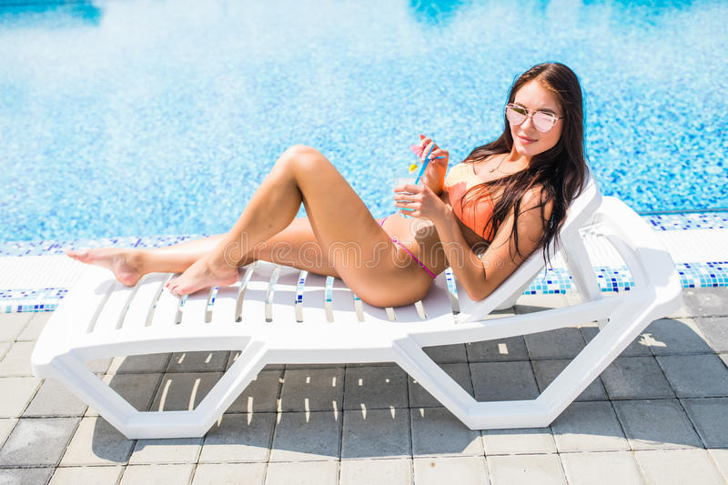 Happy young woman with cocktail laying on chaise-lounge and looking on copy space. Happy young woman with cocktail laying on chaise-longue and looking on copy stock photography