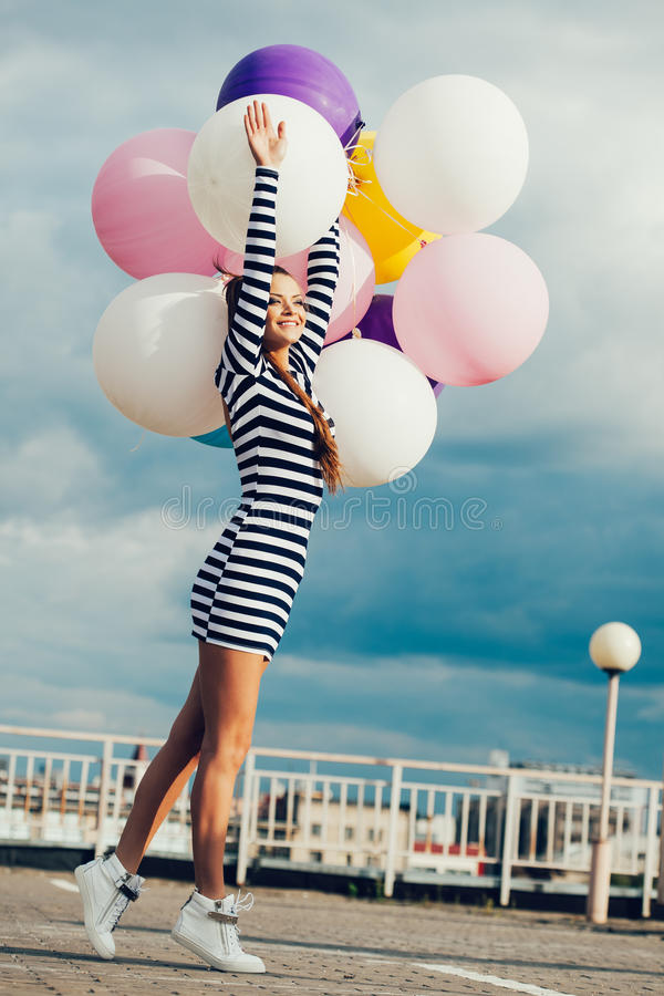 Happy young woman with colorful latex balloons. Happy young girrl with colorful latex balloons, outdoor royalty free stock photos