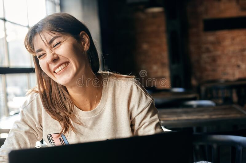 Happy young woman communicates online using computer royalty free stock photos