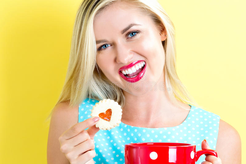 Happy young woman with cookie and coffee stock photos
