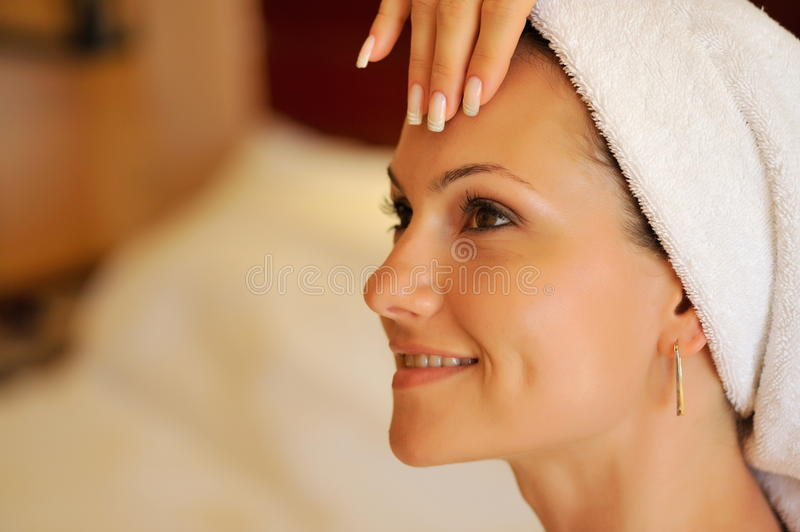Happy young woman during cosmetic treatment royalty free stock image