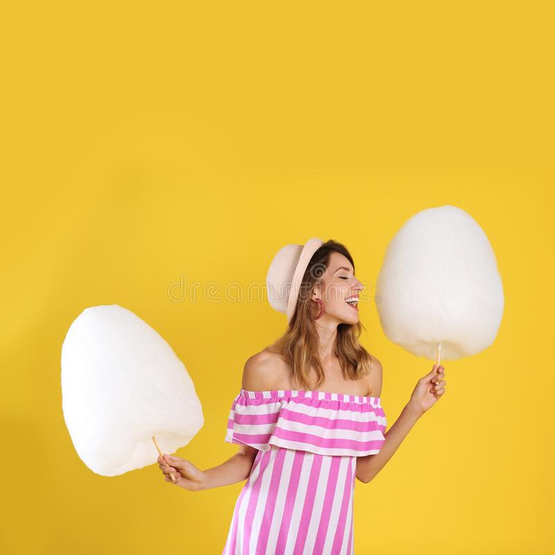 Happy young woman with cotton candies on background royalty free stock photography