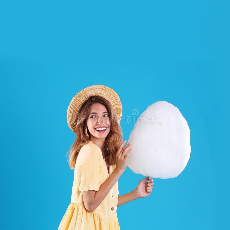 Happy young woman with cotton candy on background royalty free stock photo