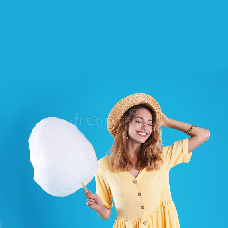 Happy young woman with cotton candy on background royalty free stock image