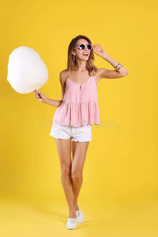 Happy young woman with cotton candy on background royalty free stock images