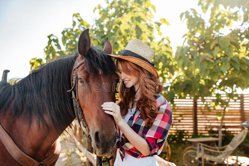 Happy young woman cowgirl standing with her horse on ranch stock images