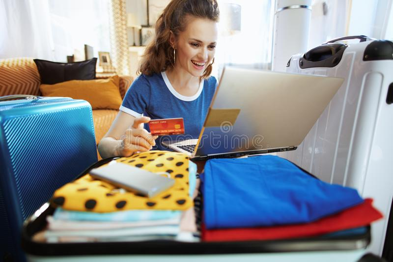 Happy young woman with credit card booking hotel room online stock photo