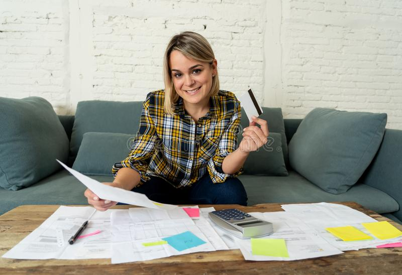 Happy young woman with credit card surrounded by papers calculating and paying bills. Attractive entrepreneur housewife woman with credit card happy free of stock photos
