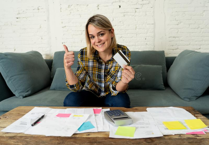 Happy young woman with credit card surrounded by papers calculating and paying bills. Attractive entrepreneur housewife woman with credit card happy free of stock photo