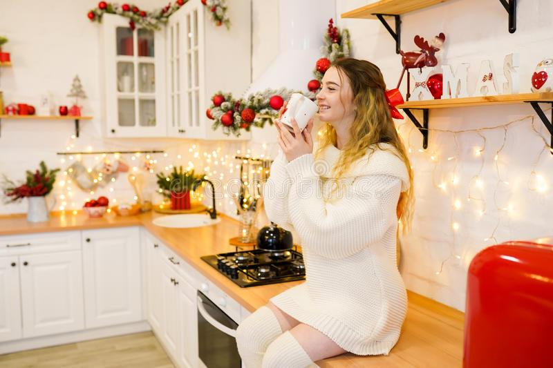 Happy young woman with cup of coffee in red christmas decorated kitchen stock photography