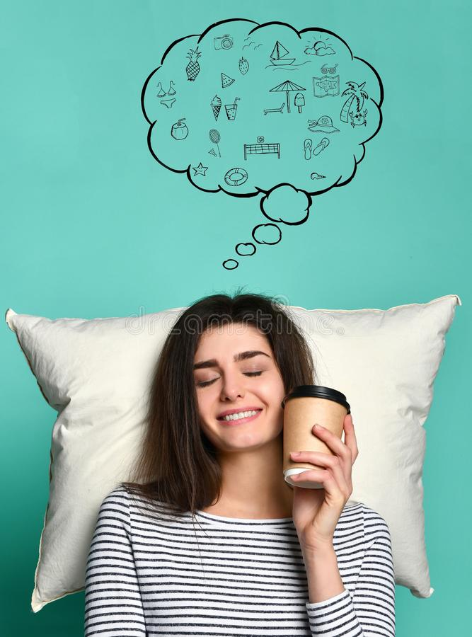 Happy young woman with a cup of coffee or tea in her hands, dreams on a pillow about anything stock photos