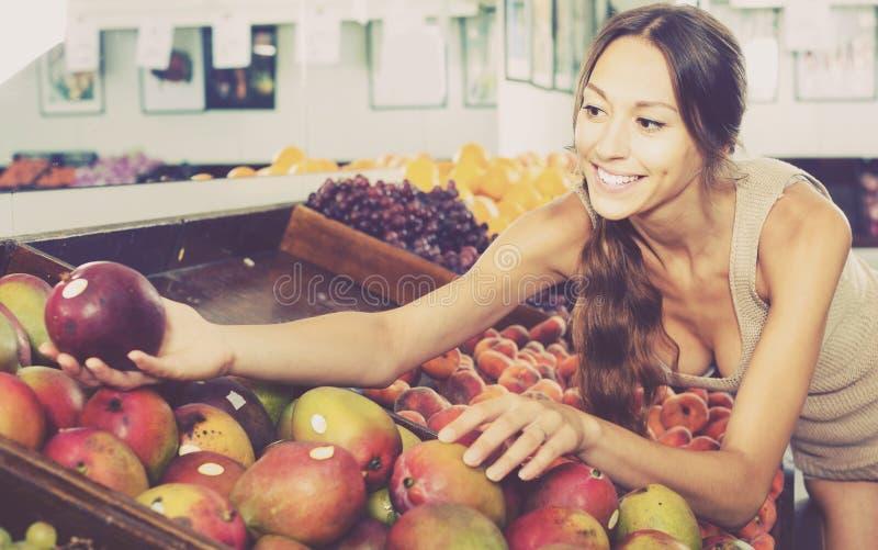 Happy young woman customer choosing ripe mango stock photos