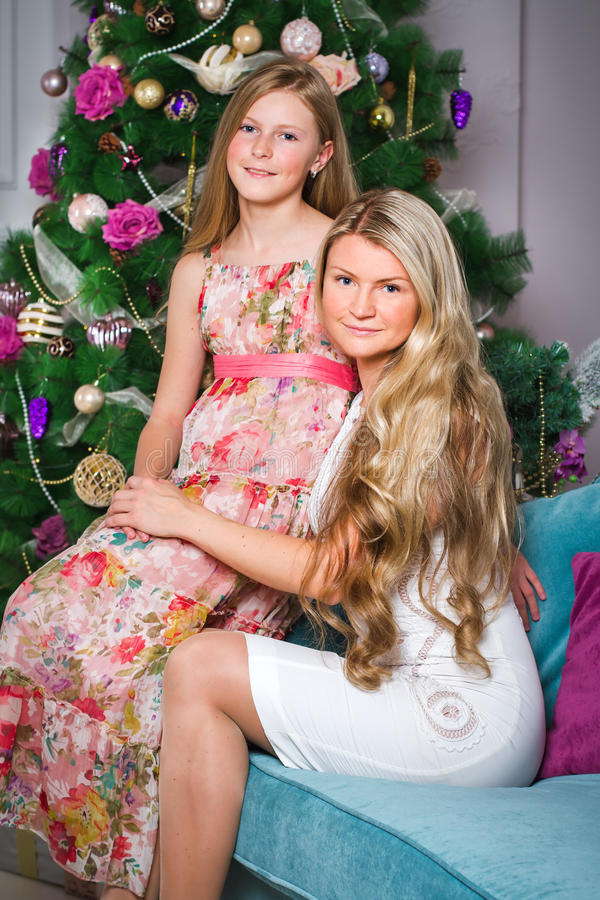 Happy young woman with cute teen daughter sitting on sofa at home stock images