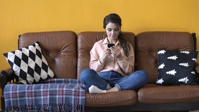 Happy young woman with dark hair in pink shirt and jeans sitting on the brown couch with pillows and typing on her stock images
