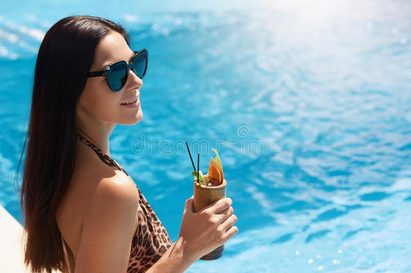 Happy young woman in dark sunglasses holding cocktail while standing next to swimming pool. Female in bikini with leopard print royalty free stock image