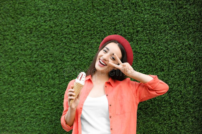 Happy young woman with delicious ice cream in waffle cone royalty free stock photography