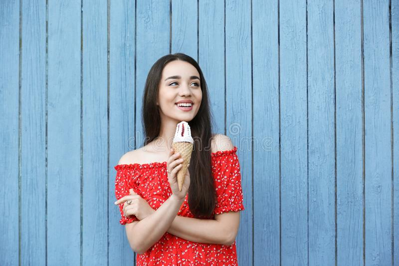 Happy young woman with delicious ice cream in waffle cone near wooden wall stock photos