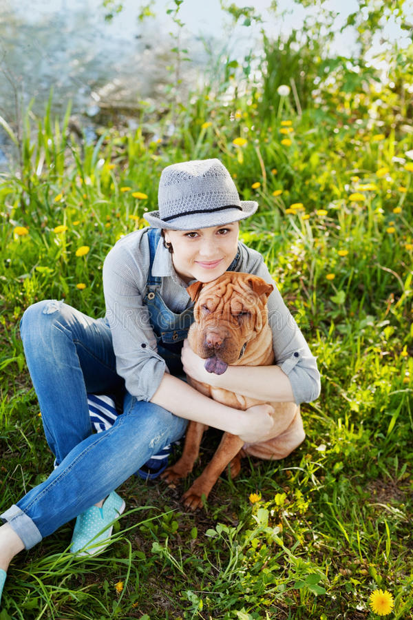 Happy young woman in denim overalls and hat hugging his beloved dog Shar Pei in the green grass in sunny day, true friends forever stock photos