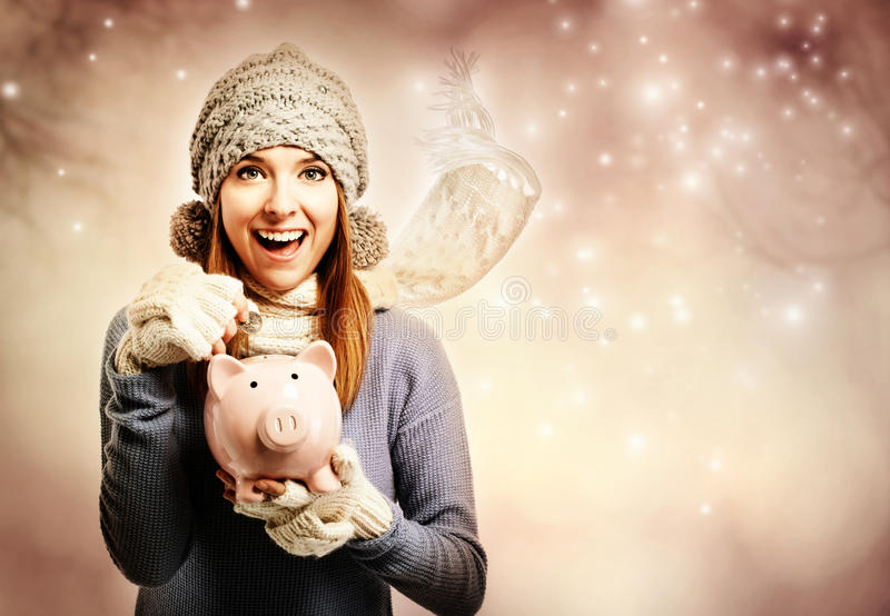 Happy young woman depositing money into her piggy bank royalty free stock photos