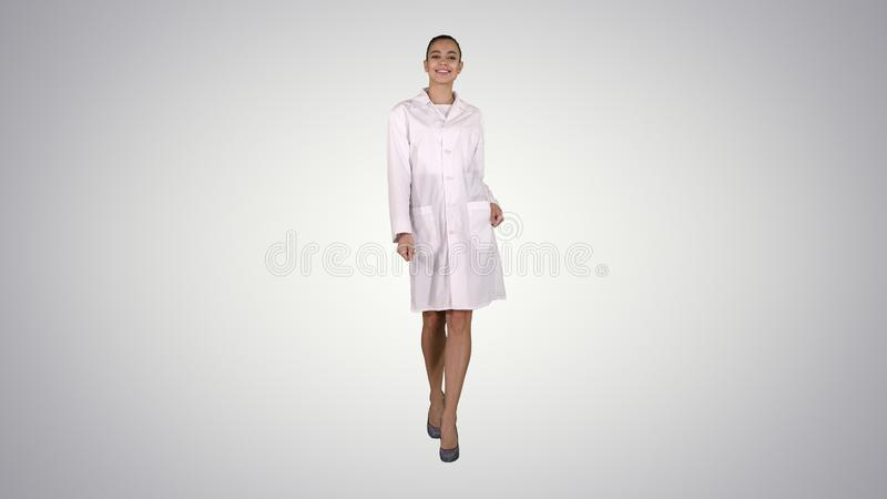Happy young woman doctor dances on gradient background. royalty free stock photography