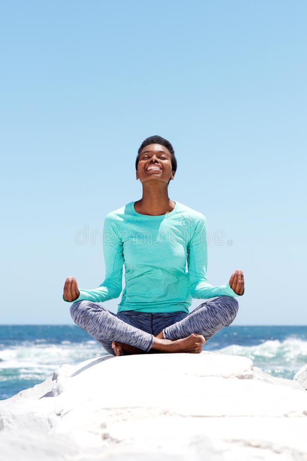Happy young woman doing yoga at the beach stock photo