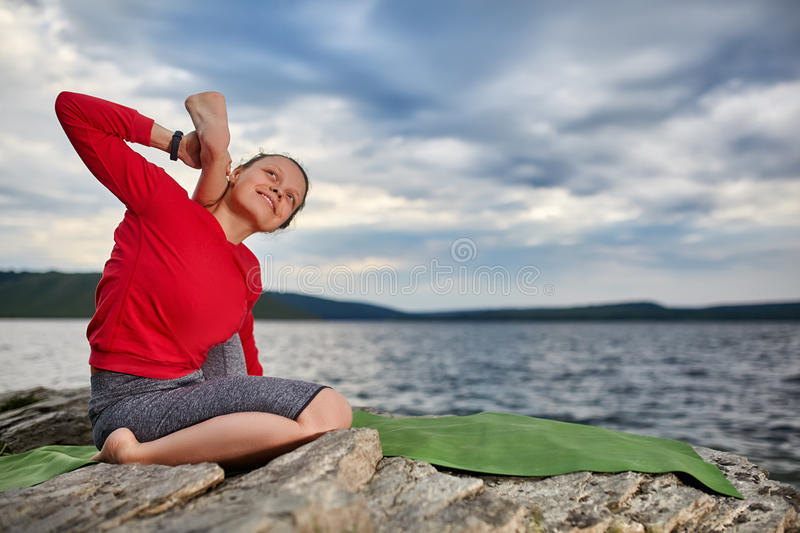 Happy young woman doing yoga exercise outdoors on the stone near river. stock images